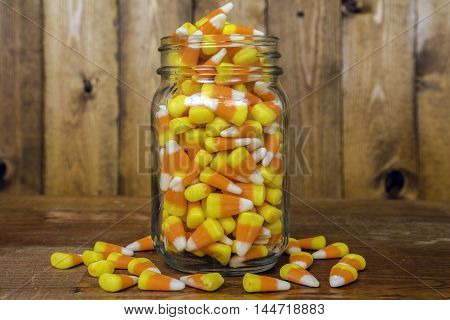 glass jar overflowing with candy corn on rustic wood background