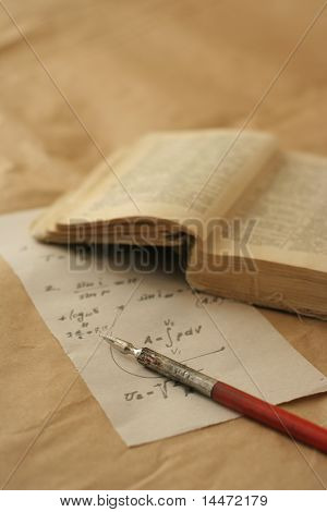 The still life photo of the old book, parchment and crow quill