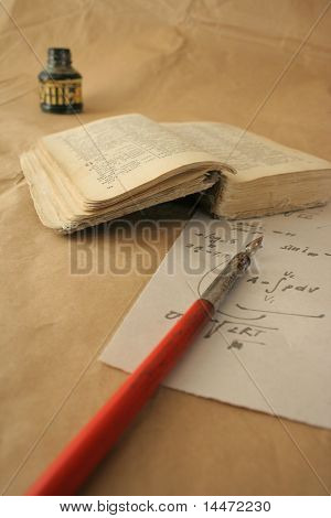 The still life photo of the old book, parchment, crow quill and bottle of the Indian ink