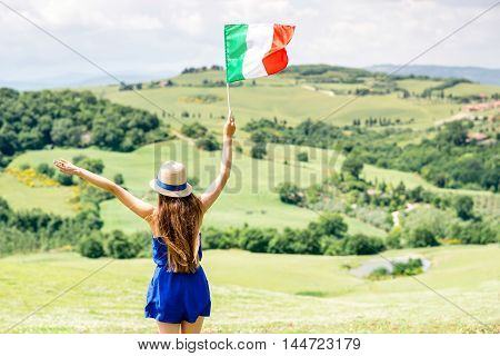 Young woman in blue dress and hat with Italian flag enjoying beautiful Tuscan landscape in Italy.