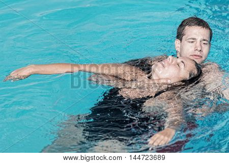 Lifeguard rescue training - young man swimming with drowning victim keeping her head above water surface