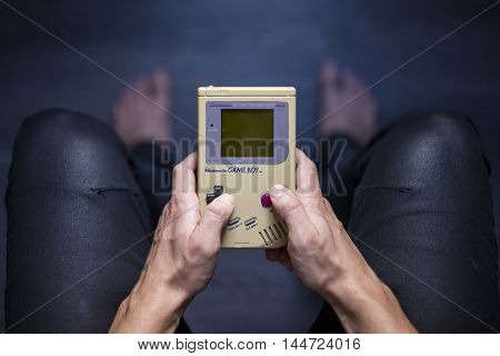 Gothenburg, Sweden - August 29, 2016: A shot from above of a young mans hands holding a Game Boy portable video game console developed by Nintendo Co., Ltd.