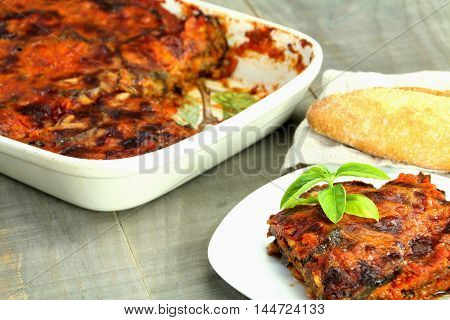 Homemade parmigiana of aubergines in a white plate. Background: parmigiana in a baking tray and bread.