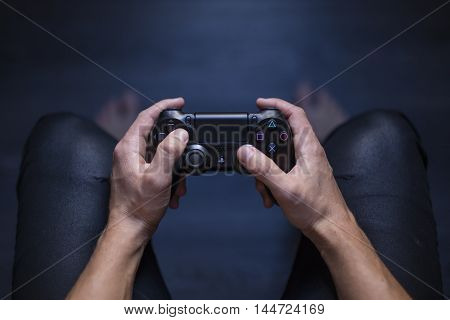 Gothenburg, Sweden - August 29, 2016: A shot from above of a young mans hands holding a video game controller for the Playstation 4, developed by Sony.