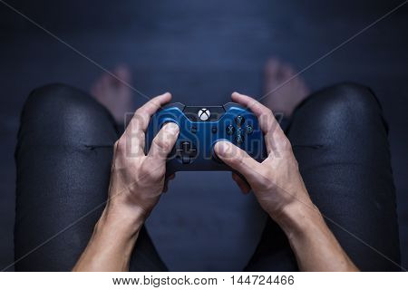 Gothenburg, Sweden - August 29, 2016: A shot from above of a young mans hands holding a blue Xbox One controller as he is playing a video game. Natural lights.