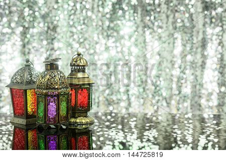 Eid and Ramadan theme background with colored lanterns against a shimmering silver glitter background