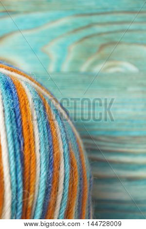 A ball of multicolor melange wool yarn for knitting crochet on wooden rustic background