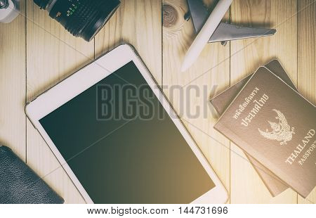 Blank tablet screen with travel equipments. Travel items and tablet on wooden table in vintage tone. Blank tablet screen for travel advertisement, travel website and travel agencies service.