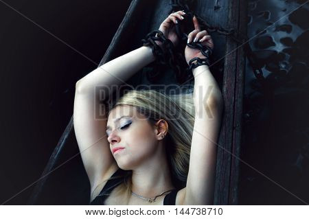 Beautiful sensual woman in a boat captivity chain. With the atmospheric effect of classic film grain