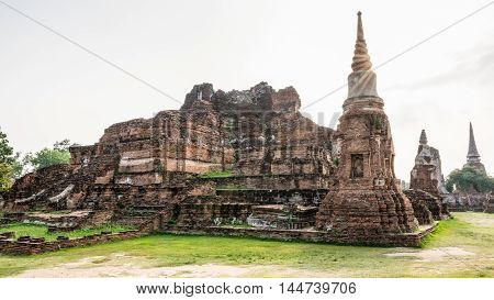Ancient ruins of pagoda under sun light at Wat Phra Mahathat temple is a famous attractions in Phra Nakhon Si Ayutthaya Historical Park Thailand