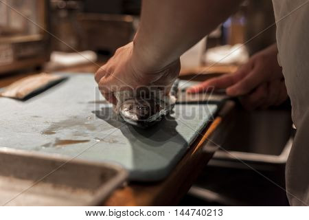 Sushi chef fillets fish for dinner service.