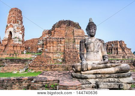 Ancient ruins of pagoda and old buddha statue at Wat Phra Mahathat temple is a famous attractions in Phra Nakhon Si Ayutthaya Historical Park Thailand