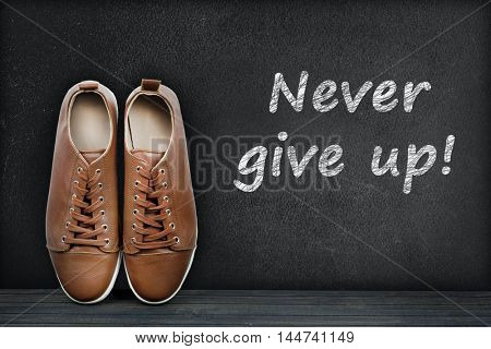 Never give up text on black board and shoes