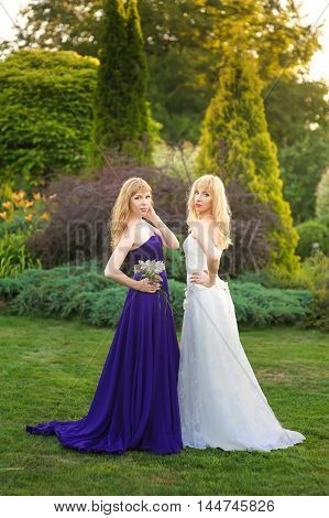 Bride and bridesmaid outside. Two girls posing on the green meadow. Bride in wedding dress. Bridesmaid in a purple evening gown.