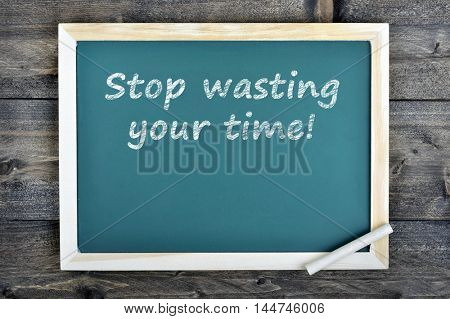 Stop wasting your time text on school board and chalk on wooden table