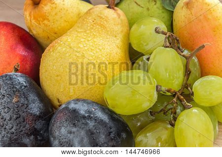 a few fresh bio grapes plums pears and nectarine on the wooden table