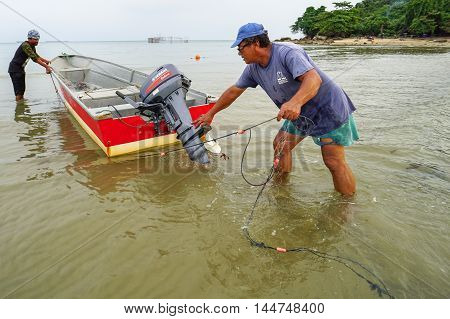 Labuan,Malaysia-Aug 28,2016: Group of fisherman with the fisherman boat and fishing net at Kiansam beach, Labuan island.Fishing is one of the occupations of people in Labuan Pear Of Borneo,Malaysia.