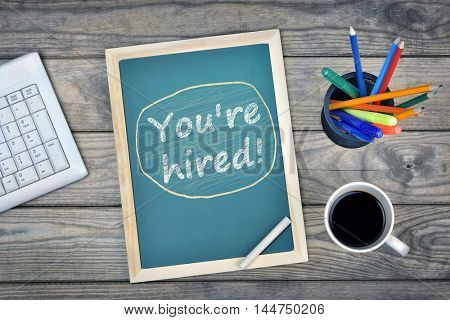 You're hired text on school board and coffee on desk