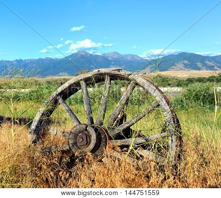 Wagon and wheels lay abandoned in deep grass along the highway in Paradise Valley Montana. The Absaroka Mountains loom in the distance.