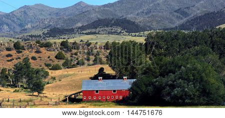 Red barn with tin roof sits in the rolling hills of the Absaroka Mountain Range in Montana.