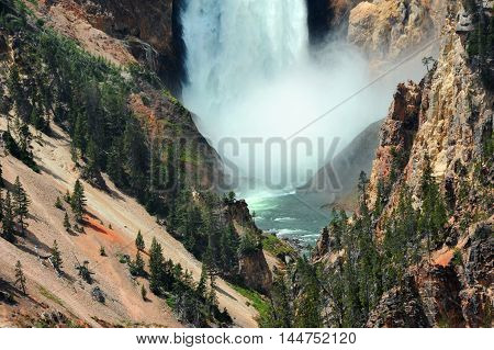 Amazing power of Lower Falls in Yellowstone National Park is shown as the thundering wall of water hits the rocks below and a spray of water rises into the air. Rock walls rise on each side.