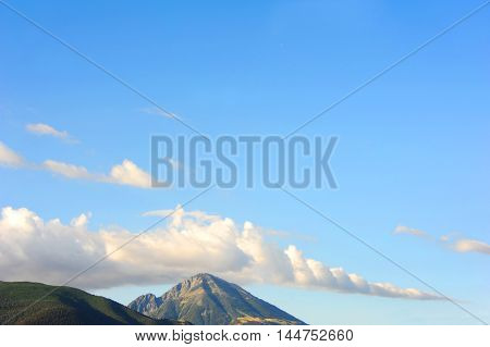 Beautiful peak rises above the Absaroka Mountain Range in Montana. Vivid blue sky and clouds fill this background image.