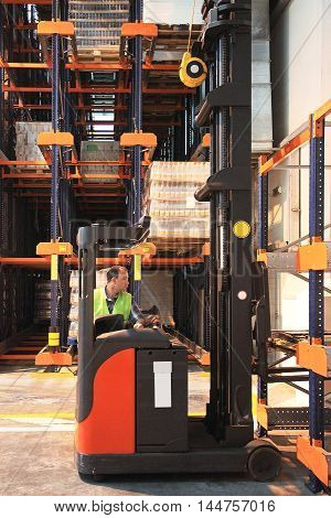 Forklift Driver Picking Up Pallet in Distribution Warehouse