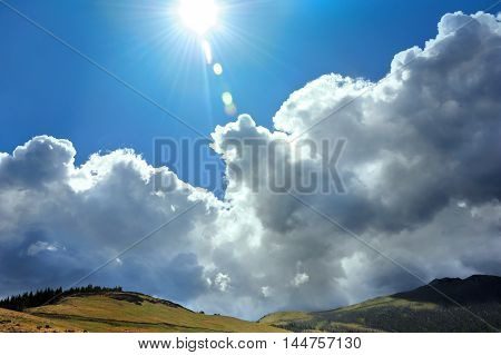 Storm clouds break before the brilliant sun rays in Yellowstone National Park. Vivid blue sky and sunshine chase the storm clouds away.