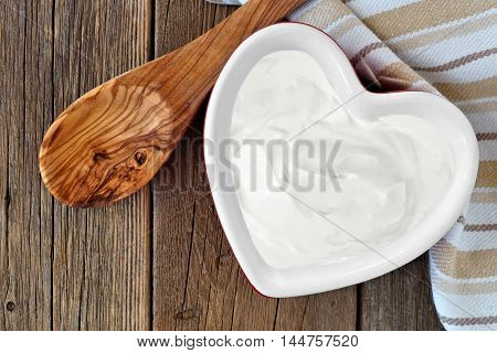 Greek Yogurt In A Heart Shaped Bowl, Overhead Scene Against A Rustic Wood Background