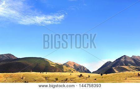Paradise Valley rises into the Absaroka Mountains in Wyoming. Blue sky and light clouds fill horizon.