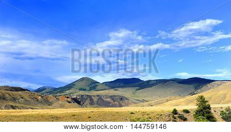 Dirt road passes through Paradise Valley in Wyoming. Road has distand view and panarama of the Absaroka Mountains.