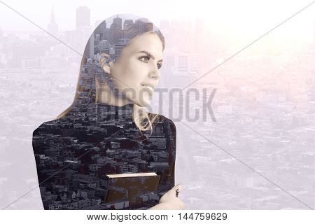 Portrait of attractive young woman with book on city background with copy space. Double exposure