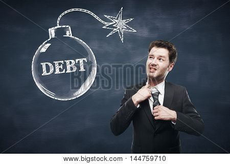 Debt concept with choking businessman and bomb sketch on textured chalkboard background