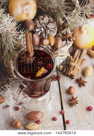 A cup of hot wine with spices and nuts Christmas card with fir-tree branches