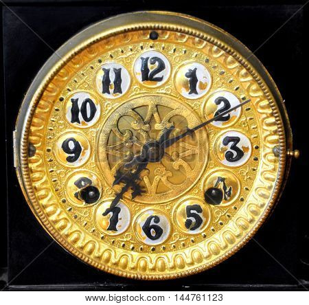 Closeup of old clock shows time at 7:10. Numbers are black and clock face is gold metal.