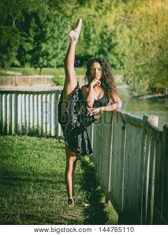 Latin dancer with black clothes dancing in a park
