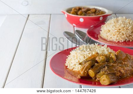 Middle Eastern Bamiya with Rice on White Table with Copy Space Horizontal