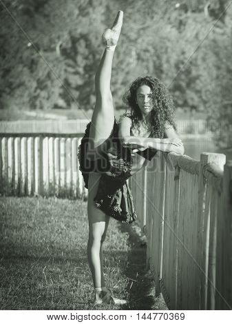 Latin dancer with black clothes lifting her leg and crossing her arms monochrome