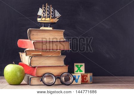 Old textbooks on the rustic wooden table on a background of black chalk board. Professorial glasses and cubes with letters.