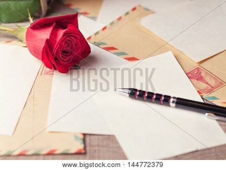 Vintage envelopes red roses and sheets of paper scattered on the wooden table for writing romantic letters.