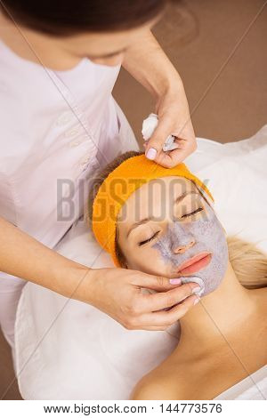 Young woman applying grey facial mask on her face