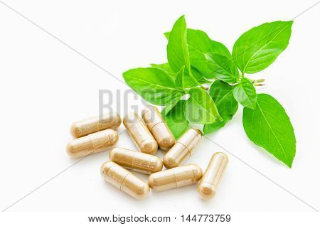 herbal drug capsule and green leaf on white background.