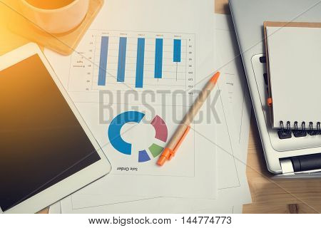 Office desk with laptop tablet black coffee and sale chart graph report Business time concept.