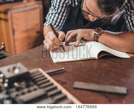 Jeweler leaning on a bench sketching out new jewelry designs in a notebook while working in his shop
