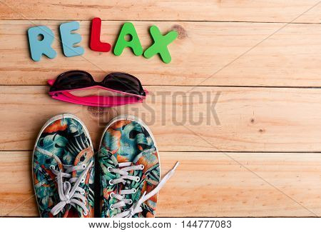 The Colorful Canvas Shoe And Sunglasses With Relax Alphabet On Wooden Background. Accessories For Tr