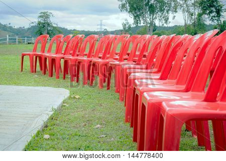 Group of red plastic chairs on the lawn.