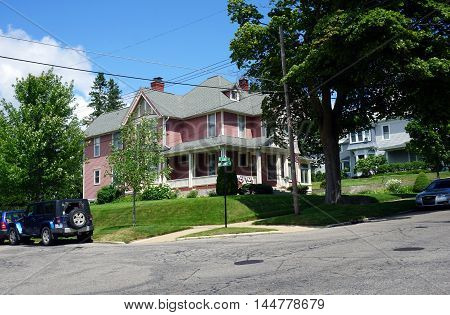 PETOSKEY, MICHIGAN / UNITED STATES - AUGUST 5, 2016: A pink Victorian mansion, with a wraparound porch, at the corner of Lake and Williams Streets near downtown Petoskey.