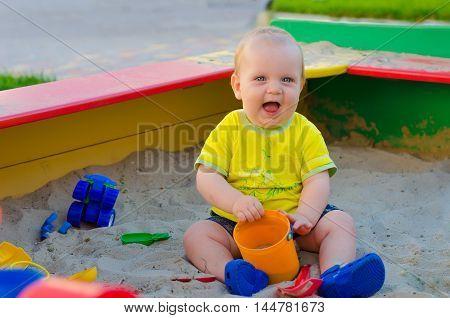 Little toddler boy playing in a sandbox