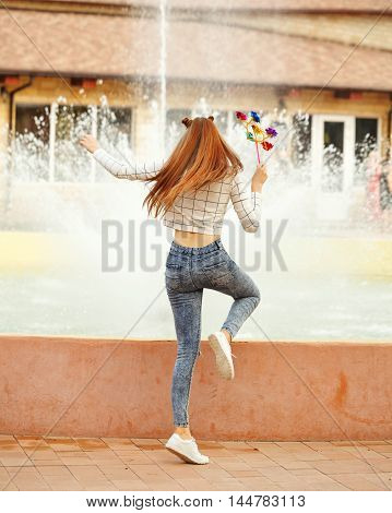 Lovely cheerful girl teenager Spinner Array Tool. Summer holidays. Flying long hair. Back view.