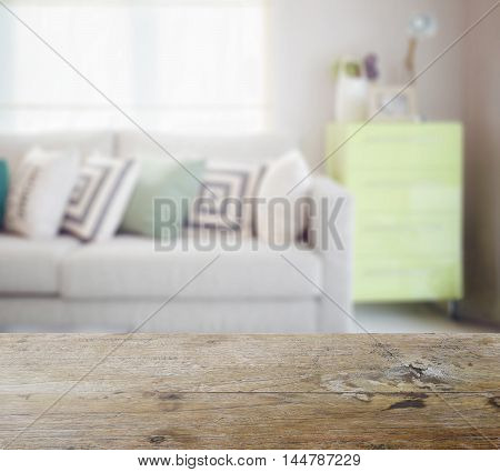 Wooden Table Top With Blur Of Geometric Pattern Pillows On Cozy Sofa And Green Sideboard In Living R